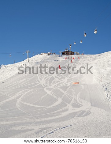 View from the bottom of a ski slope covered in snow with lifts - stock photo
