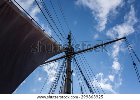 View from the bottom on the wooden ship's mast against vibrant blue sky - stock photo
