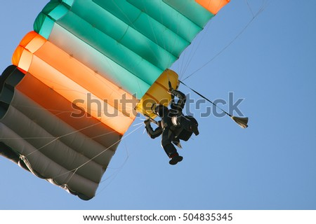 View from the bottom up to the landing a skydiver.