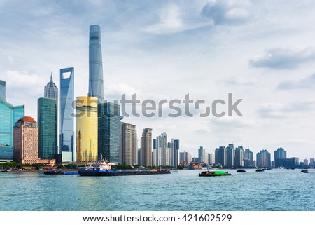 View from the Bund across the Huangpu River in Shanghai, China. The Shanghai Tower, the Shanghai World Financial Center, the Jin Mao Tower and other skyscrapers of downtown are visible at left. - stock photo