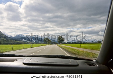 View from the car window to the road and mountain landscape. Bavarian Alps, Germany