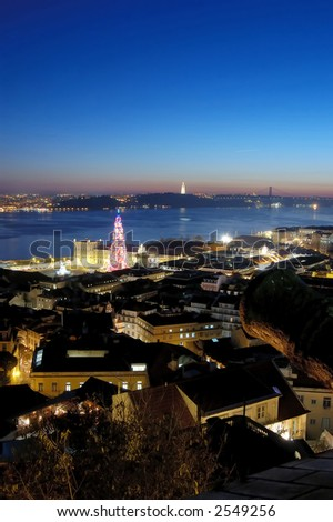 view from the castle of the city Lisbon, you can see the tagus river, the bride 25 april, the Monument at jesus crist and the bigest christmas tree of the europe - stock photo