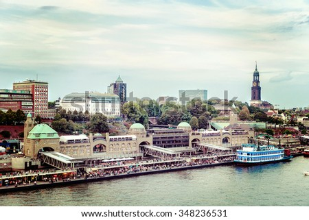 View from the Elbe to Hamburg harbor with the famous ship-landing-stages, the landmark Michel, Hotel Hafen Hamburg and old paddle steamer - stock photo
