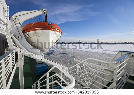 View from the Gulf of Finland covered with ice on St. Petersburg seaport and a lifeboat from a vessel in the foreground. Russia