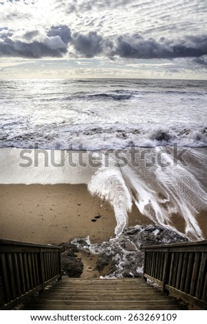 View from the high wood stairs on the wavy ocean with a white sun shining through the storm clouds, dramatic light  Bretagne,France - stock photo