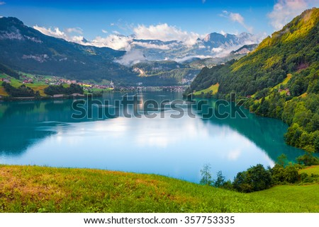 View from the hill on Lungerersee lake. Swiss village Lungern in the morning mist. Alps, Switzerland, Europe.