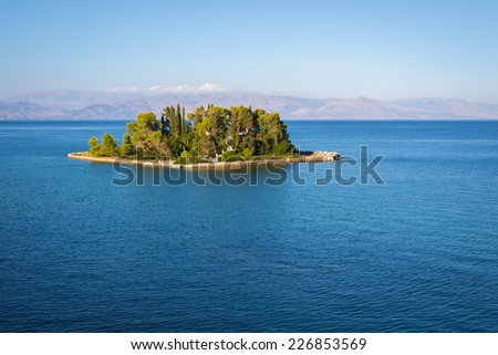 View from the hill to Pontikonisi island at Corfu Island Greece with Greek mainland mountains in the background - stock photo