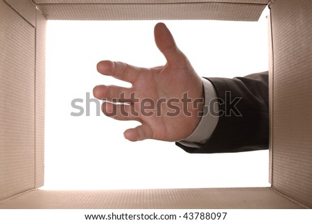 View from the inside of a cardboard box as a hand reaches in - stock photo