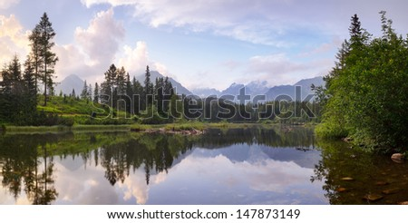 View from the mountain lake and pine forest. Slovakia, small lake Strbske Pleso