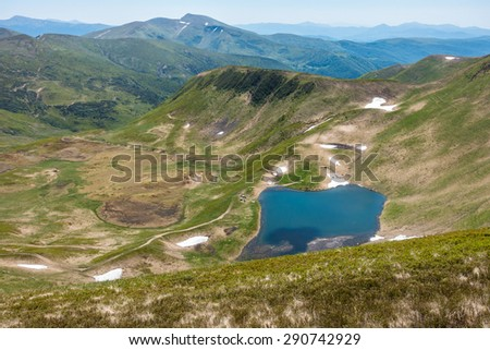 View from the mountaintop - amazing valley with lake in the spring mountains - Svydovets range, Carpathians, West Ukraine - stock photo