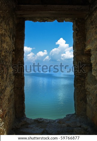 View from the old window - stone frame of landscape. Window in an old stone fortress. View from window to sea and sky. View through stone window in the wall castle.