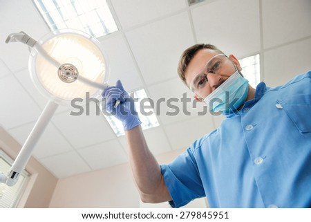 View from the patient side at the dentist. Young dentist approaching a patient and adjusting lamp in dental cabinet - stock photo