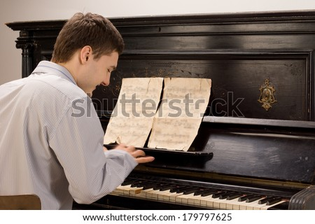 View from the rear of a young man smiling as he plays the piano using an old vintage music score on an upright wooden piano - stock photo