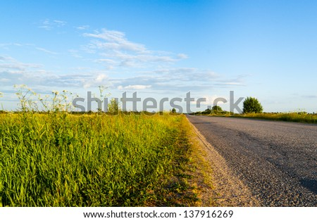 View from the side of asphalt road in coutryside in evening sunbeam - stock photo