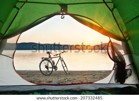 view from the tent to the lake with bicycle on sunset - stock photo