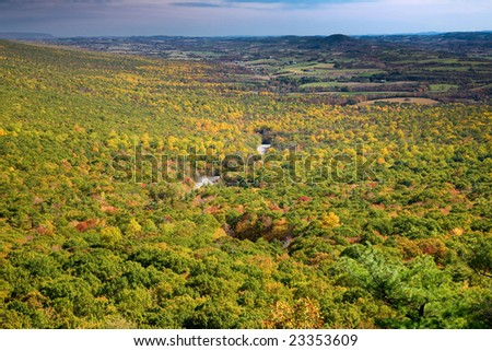 View from the top of Hawk Mountain, Pennsylvania, USA. Colorful fall foliage, river of rocks in the valley,  farmlands in the distance - stock photo