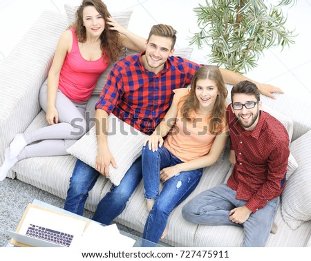 view from the top.the four friends laugh, sitting on the sofa