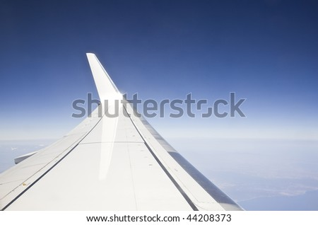 view from the window of a plane of the wing, the sky, the sea and the land - stock photo