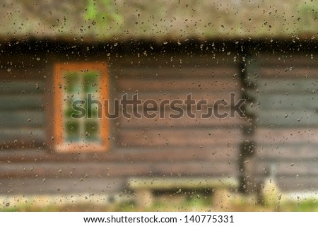 view from the window with water drops. Window of a old wooden cottage. Retro style. - stock photo