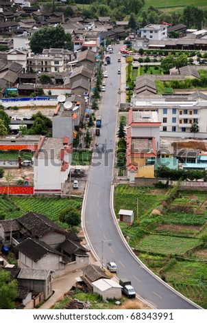 View from Tibetan mountainside looking down over a Chinese village, in Yunnan Province near Sichuan - stock photo