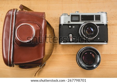 View from top of retro photography set of camera, case and lens on wooden background - stock photo