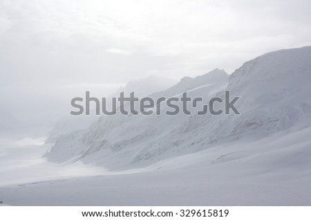 View from top of snow covered mountain. jungfrau mountain in swiss alps. - stock photo