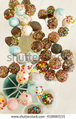 View from top on beautiful cake pops and candies decorated with sprinkles - stock photo