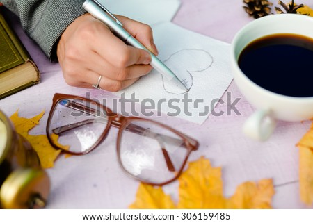 View from top on hand holding pen and drawing on napkin copy space over wooden table background, close up picture  - stock photo