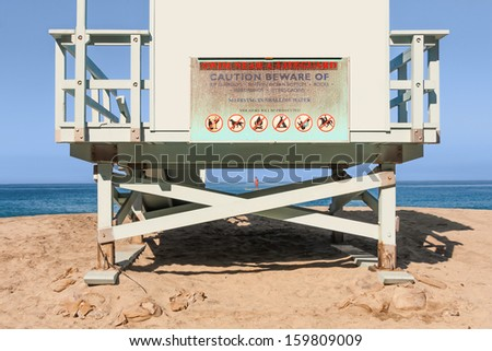 View from under the lifeguard tower. Looking at sand, blue ocean, sky from behind and underneath hut. Sign warning to swim near a lifeguard. Person paddle boarding in background. Horizontal photo. - stock photo