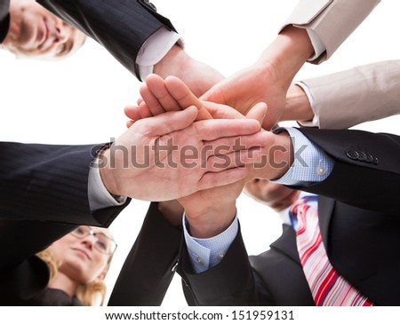 View from underneath of a group of businesspeople standing in a circle placing their hands on top of each other