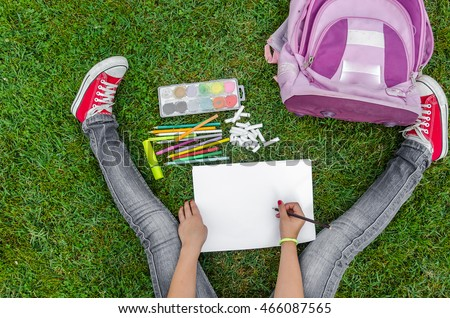 view from up on school supplies, a girl sitting on the grass and draws
