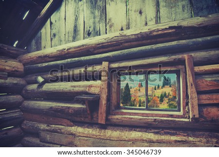 View from window of rustic wooden house to Carpathian mountain village. Ethnic cottage. Vintage colors