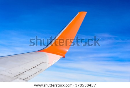 View from window seat  looking at aircraft wing flying over clouds with blue sky background - stock photo