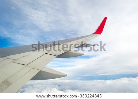 View from window seat of an airplane, wing, blue sky and clouds.