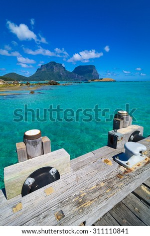 View from wooden jetty across the clear turquoise waters of Lord Howe Island Lagoon to Mt Lidgbird and Mt Gower. Australia. - stock photo