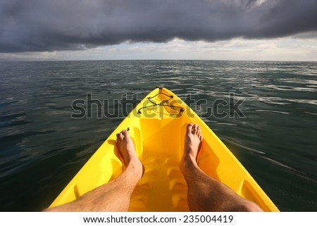 View from yellow kayak as it drifts along a beautiful, calm ocean with dark clouds ahead.