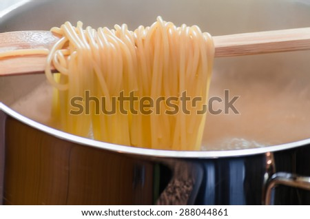 View in a saucepan with a wooden spoon hanging over the spaghetti. - stock photo