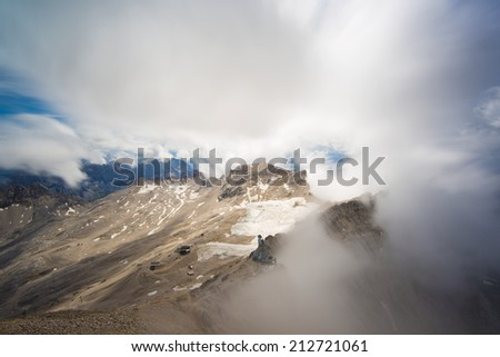 view in clouds from summit of the Zugspitze, at 2,962 meters above sea level, it is the highest peak of the Wetterstein Mountains as well as the highest mountain in Germany, Europe, long time exposure - stock photo