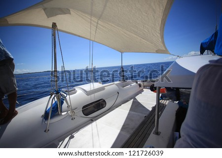View in front of a boat in the middle of calm blue sea and clear blue sky.