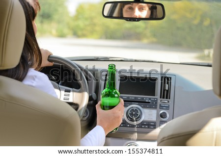 View inside a car from the back passenger seat of a woman driving holding a bottle of alcohol in one hand while steering - stock photo