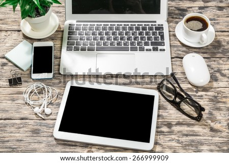 View. Laptop, smartphone, tablet and coffee cup with financial documents on wooden table - stock photo