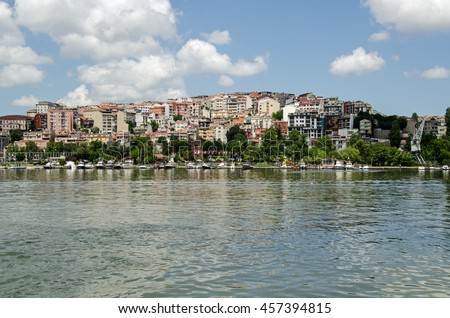 View looking north across the Golden Horn towards boats and homes in the Beyoglu district of Istanbul, Turkey on a sunny afternoon.