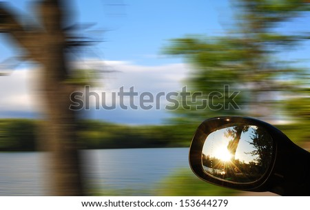view mirrors in cars at the setting sun, blurred landscape - stock photo