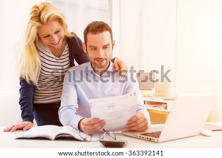 View of a Attractive couple doing administrative paperwork - stock photo