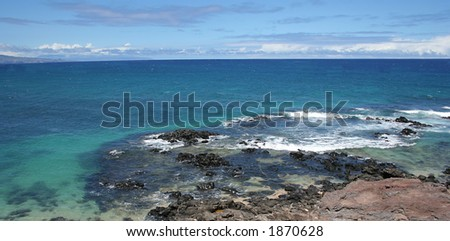 View of a beach cove on Maui's northshore, with blue and green ocean with clouds
