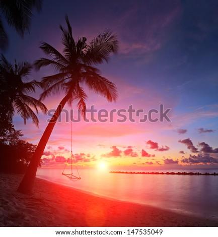 View of a beach with palm trees and swing at sunset, Kuredu island, Maldives, Lhaviyani atoll - stock photo