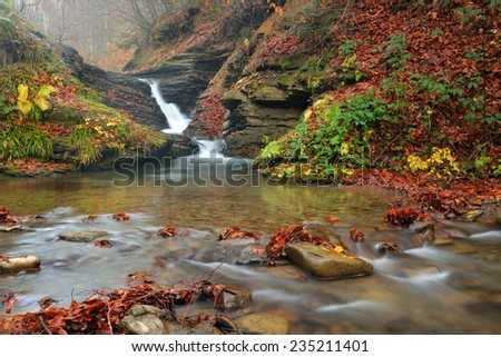 View of a beautiful autumn creek with waterfall - stock photo