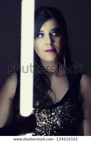 View of a beautiful girl in dark leather clothes holding a light tube.