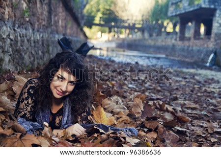 View of a beautiful girl in the middle of autumn leaves.