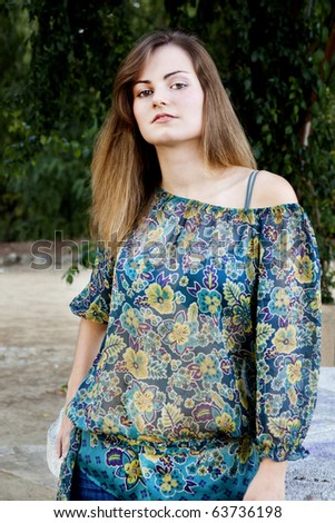 View of a beautiful girl on a floral dress on a park.